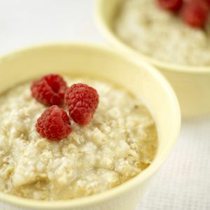bowl of oatmeal with 3 raspberries on top